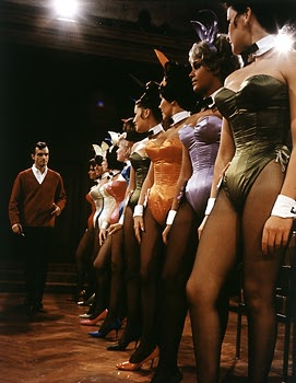 Hugh Hefner inspecting a new design for the Bunny costume at the Chicago Playboy Mansion.